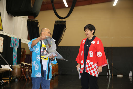 Director Ross Iwamoto presenting Ikebana calendar to event coordinator Heather Nagami